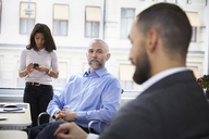 Mature businessman explaining with colleague in meeting at office - MASF08882