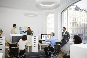 Businesswoman sharing ideas with male and female coworkers in meeting at office - MASF08891