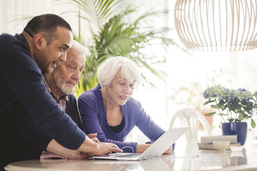 Mature man using laptop with parents at table in nursing home - MASF08918