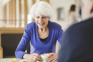 Senior woman smiling while having drink at table with man in nursing home - MASF08924