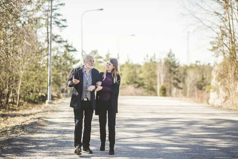 Full length of young woman walking arm in arm with grandfather on road - MASF08930