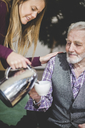 Young woman pouring drink in cup being held by grandfather in nursing home - MASF08939