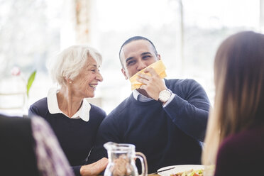 Cheerful senior woman with son wiping mouth with tissue paper while having lunch in nursing home - MASF08945