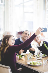 Young woman taking selfie with father and grandparents while having lunch in nursing home - MASF08948