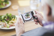 Cropped image of senior man photographing food through mobile phone at table - MASF08954