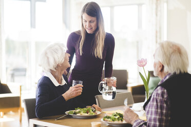 Young woman talking with grandmother while grandfather having meal at table in nursing home - MASF08957