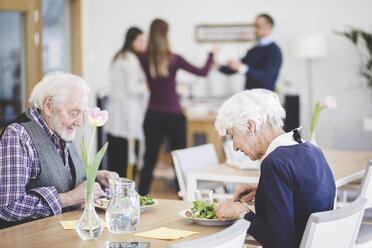 Senior couple eating lunch while at table in nursing home - MASF08960