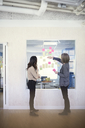 Side view of female business professionals discussing over adhesive notes stuck on glass in office - MASF08987