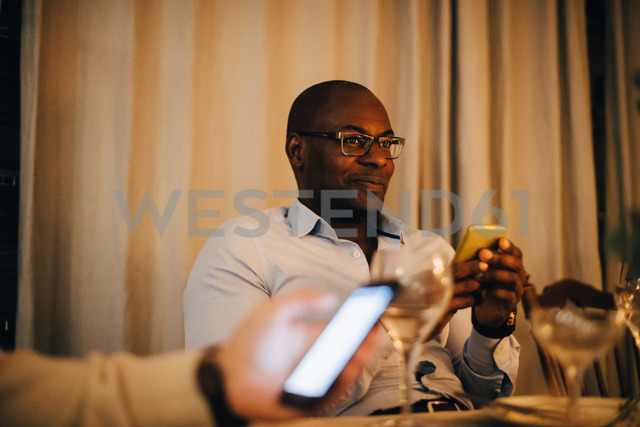 Smiling mature man using mobile phone while sitting with friend at dining table - MASF09026 - Maskot ./Westend61