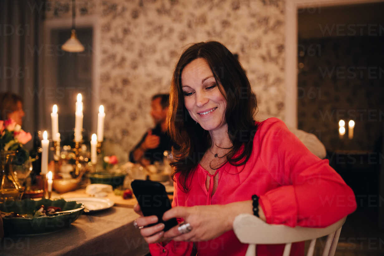 Smiling woman using mobile phone while sitting with friends in dinner party - MASF09029 - Maskot ./Westend61