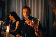 Man drinking wine while sitting with female friends at dinner party - MASF09032
