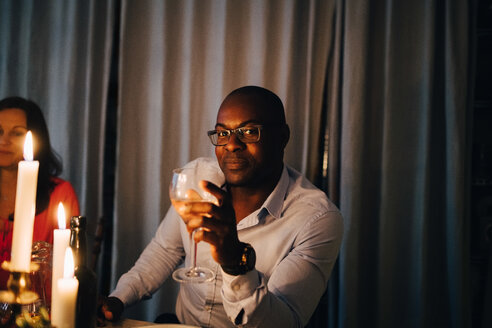 Portrait of mature man having drink while sitting with friend at dinner party - MASF09035