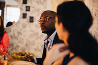 Close-up of mature man talking to friend during dinner party - MASF09041