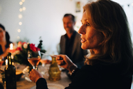 Close-up of woman raising toast with wineglass during dinner party - MASF09044