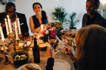 Woman raising toast with wineglass in dinner party at home - MASF09047