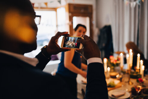 Man photographing friends through smart phone at dinner party - MASF09053