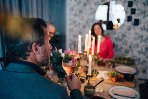 Mature man having wine while sitting with friends at dinner party - MASF09056