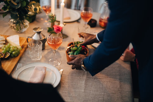 Midsection of man serving food to friend at dinning table in dinner party - MASF09059