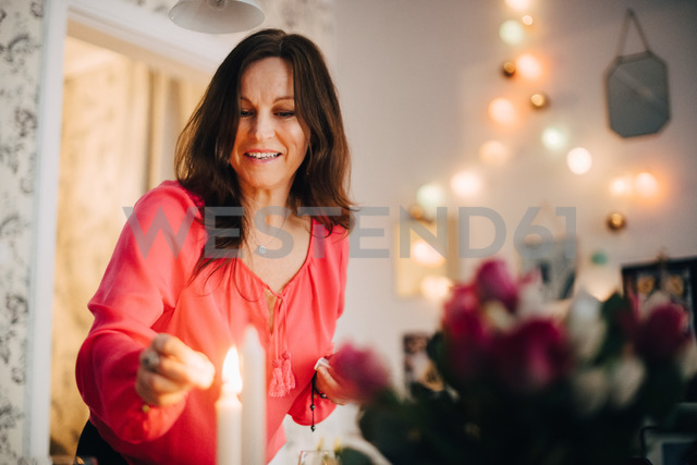 Happy mature woman igniting candle in party at home - MASF09068