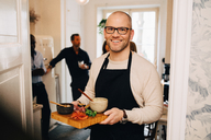 Portrait of man holding food in serving tray while standing at doorway - MASF09080