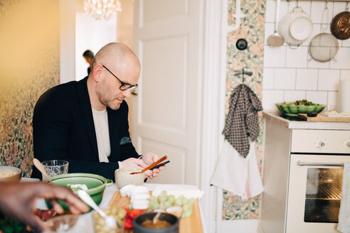 Mature man using mobile phone while sitting at dining table during party - MASF09095