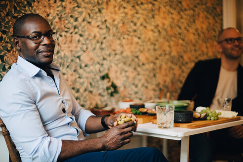 Portrait of man having food while sitting with friend by wall at home - MASF09107