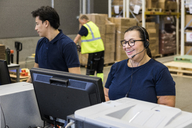 Smiling mature female customer service representative talking through headset while standing by coworker in distribution - MASF09110