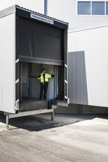 Full length of young male worker gesturing while standing on warehouse entrance - MASF09116