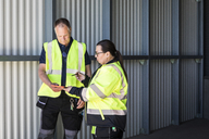 Warehouse workers discussing over digital tablet while standing at entrance - MASF09119