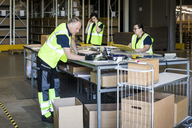 Multi-ethnic workers packing merchandise at distribution warehouse - MASF09125