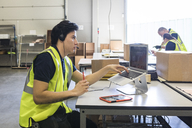 Confident young male customer service representative looking away while sitting with laptop at desk in warehouse - MASF09134