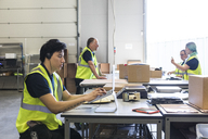 Confident young male customer service representative using laptop while coworkers discussing at desk in warehouse - MASF09137