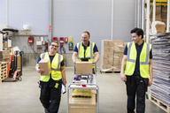 Smiling multi-ethnic coworkers walking with cart at distribution warehouse - MASF09143