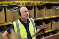 Senior male worker with digital tablet looking away while talking on headset against rack at distribution warehouse - MASF09146