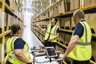 Young worker discussing with coworkers with cart while standing on aisle amidst racks at distribution warehouse - MASF09170