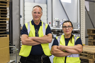 Portrait of confident coworkers standing with arms crossed in distribution warehouse - MASF09173