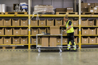 Full length side view of senior male worker pushing cart with cardboard boxes by rack at distribution warehouse - MASF09176
