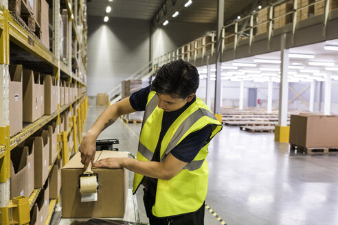 Young male worker packing cardboard box with adhesive tape at distribution warehouse - MASF09179