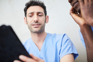 Low angle view of male nurses discussing over digital tablet at hospital - MASF09197