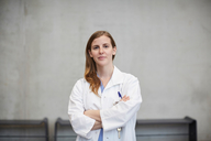 Portrait of confident female doctor standing with arms crossed against wall at hospital - MASF09209