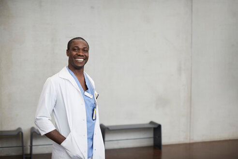 Portrait of smiling male doctor standing with hands in pockets against wall at hospital - MASF09212