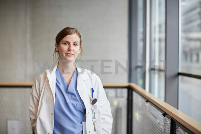 Portrait of confident mid adult female doctor by window in corridor at hospital - MASF09215