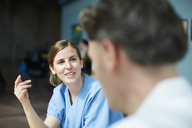 Smiling female nurse discussing with mature doctor while sitting at cafeteria in hospital - MASF09227