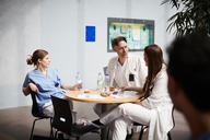 Confident mature doctor discussing with female coworkers while sitting at table in hospital cafeteria - MASF09230