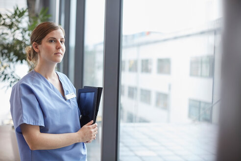 Thoughtful female nurse looking through window while standing in corridor at hospital - MASF09242