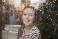 Portrait happy girl at wet window in Christmas living room - HOXF03799