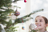 Smiling girl looking up at ornaments on Christmas tree - HOXF03802