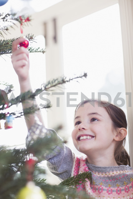 Smiling, curious girl touching ornament on Christmas tree - HOXF03811