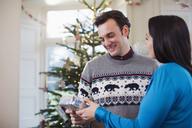 Wife giving Christmas gift to husband - HOXF03829