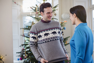 Husband showing Christmas sweater to wife - HOXF03856